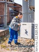 Электрик проверяет оборудование на подстанции высокого напряжения. Стоковое фото, фотограф Станислав Илюк / Фотобанк Лори