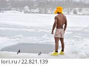 Темнокожий мужчина в трусах и ушанке стоит возле проруби. Стоковое фото, фотограф VIACHESLAV KRYLOV / Фотобанк Лори