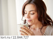 happy woman with cup of tea or coffee at home. Стоковое фото, фотограф Syda Productions / Фотобанк Лори