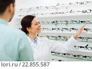 Купить «optician showing glasses to man at optics store», фото № 22855587, снято 25 ноября 2015 г. (c) Syda Productions / Фотобанк Лори