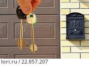 Купить «Ключи от квартиры в руке на фоне  жилого дома», фото № 22857207, снято 21 апреля 2016 г. (c) Сергеев Валерий / Фотобанк Лори