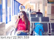 Купить «Молодые женщина разговаривает по телефону  в аэропорту», фото № 22901559, снято 26 мая 2019 г. (c) Дарья Петренко / Фотобанк Лори