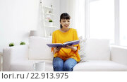 Купить «smiling young asian woman reading book at home», видеоролик № 22913975, снято 13 марта 2016 г. (c) Syda Productions / Фотобанк Лори