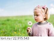 Маленькая девочка дует на пушистый одуванчик. Стоковое фото, фотограф Dmytro Kohut / Фотобанк Лори