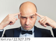 Купить «Лысый мужчина напряженно думает», фото № 22927379, снято 25 октября 2015 г. (c) Александр Лычагин / Фотобанк Лори