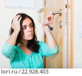 Купить «Brunette looking at broken lock of door», фото № 22928403, снято 16 октября 2019 г. (c) Яков Филимонов / Фотобанк Лори