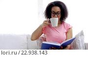 Купить «african woman reading book and drinking tea», видеоролик № 22938143, снято 10 мая 2016 г. (c) Syda Productions / Фотобанк Лори