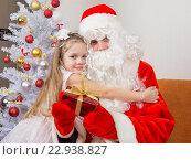 Купить «Маленькая девочка обнимает деда мороза который держит подарок», фото № 22938827, снято 24 января 2016 г. (c) Иванов Алексей / Фотобанк Лори