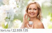 happy woman applying cream to her face. Стоковое фото, фотограф Syda Productions / Фотобанк Лори