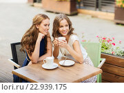 Купить «young women drinking coffee and talking at cafe», фото № 22939175, снято 9 августа 2015 г. (c) Syda Productions / Фотобанк Лори