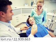 Купить «happy dentist showing toothbrush to patient girl», фото № 22939663, снято 23 мая 2015 г. (c) Syda Productions / Фотобанк Лори