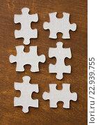 Купить «close up of puzzle pieces on wooden surface», фото № 22939755, снято 21 апреля 2016 г. (c) Syda Productions / Фотобанк Лори