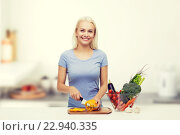 smiling young woman chopping vegetables on kitchen. Стоковое фото, фотограф Syda Productions / Фотобанк Лори
