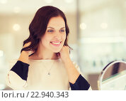 Купить «happy woman choosing pendant at jewelry store», фото № 22940343, снято 30 апреля 2015 г. (c) Syda Productions / Фотобанк Лори