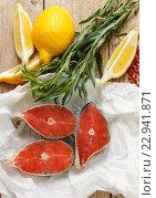 Лимон, стейки из лосося и тархун на деревянном столе. Стоковое фото, фотограф Виктория Панченко / Фотобанк Лори