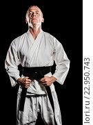 Купить «Fighter tightening karate belt», фото № 22950743, снято 15 октября 2015 г. (c) Wavebreak Media / Фотобанк Лори