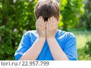 Купить «teen problems - boy covered his face with his hands outside», фото № 22957799, снято 15 мая 2016 г. (c) Володина Ольга / Фотобанк Лори