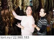 Купить «Two customers purchasing hair extension», фото № 22980183, снято 17 октября 2018 г. (c) Яков Филимонов / Фотобанк Лори