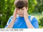 Купить «Boy teenager with headache on nature», фото № 22984339, снято 15 мая 2016 г. (c) Володина Ольга / Фотобанк Лори