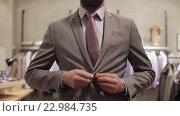 Купить «happy young man trying suit at clothing store», видеоролик № 22984735, снято 8 апреля 2016 г. (c) Syda Productions / Фотобанк Лори