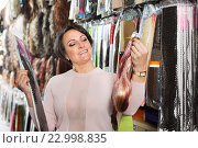 Купить «Cheerful smiling middle aged woman purchasing hair extension», фото № 22998835, снято 17 октября 2018 г. (c) Яков Филимонов / Фотобанк Лори