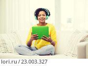 Купить «happy african woman with tablet pc and headphones», фото № 23003327, снято 4 июня 2015 г. (c) Syda Productions / Фотобанк Лори