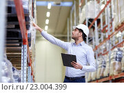Купить «happy businessman with clipboard at warehouse», фото № 23004399, снято 9 декабря 2015 г. (c) Syda Productions / Фотобанк Лори