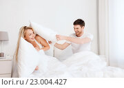 Купить «happy couple having pillow fight in bed at home», фото № 23004427, снято 25 февраля 2016 г. (c) Syda Productions / Фотобанк Лори