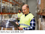 Купить «man with clipboard in safety vest at warehouse», фото № 23004727, снято 9 декабря 2015 г. (c) Syda Productions / Фотобанк Лори