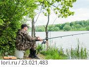 Купить «Мужчина ловит рыбу на берегу озера», эксклюзивное фото № 23021483, снято 27 мая 2016 г. (c) Игорь Низов / Фотобанк Лори