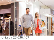 Купить «happy young couple with shopping bags in mall», фото № 23036407, снято 10 ноября 2014 г. (c) Syda Productions / Фотобанк Лори