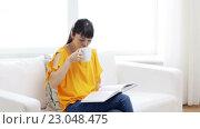 Купить «smiling young asian woman reading book at home», видеоролик № 23048475, снято 13 марта 2016 г. (c) Syda Productions / Фотобанк Лори