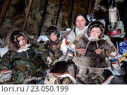Купить «A Nenets herder woman inside her tent / Chum with her girl and her two boys. The whole familly is wearing winter coat made with reindeer skin and fur,...», фото № 23050199, снято 18 апреля 2016 г. (c) age Fotostock / Фотобанк Лори