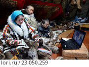 Nenets children, two boys and a teenager girl, looking at a movie on a computer inside their tent / Chum. The girl is also sewing reindeer skin / fur.... (2016 год). Редакционное фото, фотограф Eric Baccega / age Fotostock / Фотобанк Лори