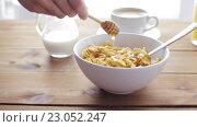 Купить «hand adding honey to corn flakes for breakfast», видеоролик № 23052247, снято 15 апреля 2016 г. (c) Syda Productions / Фотобанк Лори