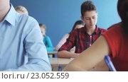Купить «students with notebooks writing test at school», видеоролик № 23052559, снято 28 апреля 2016 г. (c) Syda Productions / Фотобанк Лори
