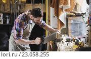 Купить «carpenter working with saw and wood at workshop», видеоролик № 23058255, снято 21 мая 2016 г. (c) Syda Productions / Фотобанк Лори