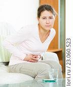 Купить «Portrait of girl folding up with belly pain indoor», фото № 23060523, снято 13 декабря 2019 г. (c) Яков Филимонов / Фотобанк Лори