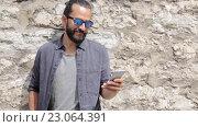 Купить «Man texting message on smartphone at stone wall», видеоролик № 23064391, снято 3 июня 2016 г. (c) Syda Productions / Фотобанк Лори