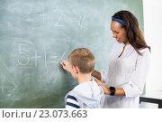 Купить «Smiling teacher assisting boy in doing addition on chalkboard», фото № 23073663, снято 6 марта 2016 г. (c) Wavebreak Media / Фотобанк Лори