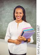 Купить «Portrait of smiling school teacher holding books in classroom», фото № 23073667, снято 6 марта 2016 г. (c) Wavebreak Media / Фотобанк Лори