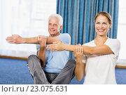 Instructor helping senior man with sport exercises. Стоковое фото, агентство Wavebreak Media / Фотобанк Лори