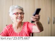 Купить «Senior woman using a remote control», фото № 23075667, снято 2 марта 2016 г. (c) Wavebreak Media / Фотобанк Лори
