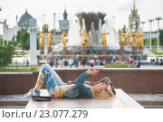 """Купить «Две девушки отдыхают теплым июньским днем на парапете Центрального павильона ВДНХ на фоне фонтана """"Дружба народов""""», фото № 23077279, снято 10 июня 2016 г. (c) Сайганов Александр / Фотобанк Лори"""