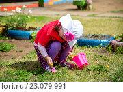 Маленькая девочка срывает цветок. Стоковое фото, фотограф Виктор Хван / Фотобанк Лори