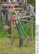 Купить «Две лопаты с оранжевыми пластиковыми ручками стоят на дачном участке на фоне старых досок», фото № 23080703, снято 4 июня 2016 г. (c) Наталья Николаева / Фотобанк Лори
