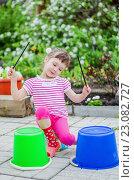 Маленькая девочка играет на ведрах как на барабанах на улице. Стоковое фото, фотограф Сергей Завьялов / Фотобанк Лори