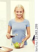 Купить «smiling woman cooking vegetable salad at home», фото № 23083299, снято 26 апреля 2015 г. (c) Syda Productions / Фотобанк Лори