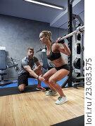 Купить «man and woman with bar flexing muscles in gym», фото № 23083575, снято 19 апреля 2015 г. (c) Syda Productions / Фотобанк Лори