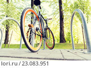 Купить «close up of bicycle locked at street parking», фото № 23083951, снято 30 мая 2015 г. (c) Syda Productions / Фотобанк Лори